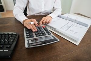 Close-up Of Businessperson Calculating Financial Expenses With Calculator At Desk